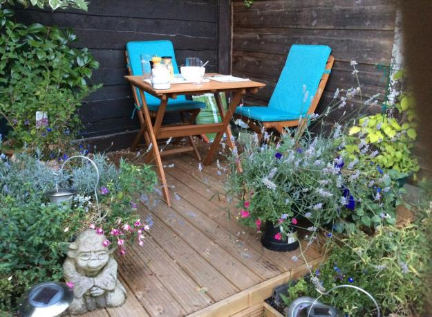 two ch air bistro set with aqua cushions among summer flowers - stone yoda on corner of decking