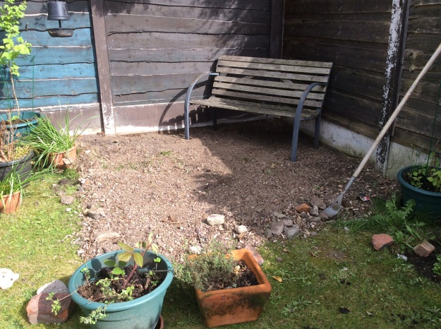 wooden and metal garden bench in corner of garden on shingle